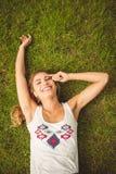 Надземный портрет жизнерадостной женщины лежа на траве Стоковые Фото