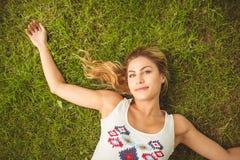 Надземный портрет усмехаясь женщины лежа на траве Стоковое Фото