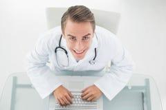 Надземный портрет усмехаясь доктора используя компьтер-книжку Стоковое Изображение