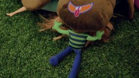 На искусственной зеленой траве в комнате детей, на поле, лежит смешная коричневая мягкая игрушка сток-видео