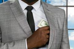 Наличные деньги черного работника офиса пряча Стоковые Фотографии RF