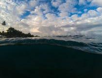 Над и под водораздел в тропическом seashore Темная морская вода и солнечное небо Стоковое Изображение RF
