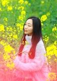 На красивой предыдущей весне, стойка молодой женщины в середине желтых цветков рапса хранила которая самые большие в Шанхае Стоковые Изображения RF