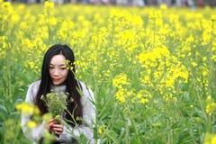 На красивой предыдущей весне, стойка молодой женщины в середине желтых цветков рапса хранила которая самые большие в Шанхае Стоковая Фотография RF