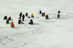 На льде реки рыболовы приниманнсяая за рыбная ловля Стоковое фото RF