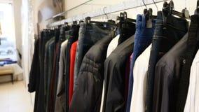 На магазине одежды Строка людей и одежды женщин куртки, джинсы и рубашки на вешалках Собрание новое красивого сток-видео