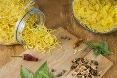 На макаронных изделиях деревянного стола разных видов и специй для варить макаронные изделия Простая еда деревни Стоковое Фото