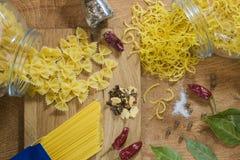 На макаронных изделиях деревянного стола разных видов и специй для варить макаронные изделия Простая еда деревни Стоковая Фотография