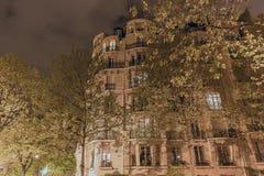 На ноче высокорослый красивый дом окруженный высокими деревьями загорен фонариками Стоковая Фотография