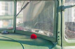 На лобовом стекле военного транспортного средства цветет красные гвоздики Стоковое фото RF