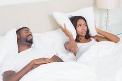 Надоеданная женщина покрывая ее уши с подушками для того чтобы преградить вне храпеть Стоковые Изображения