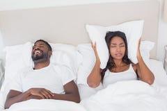 Надоеданная женщина покрывая ее уши с подушками Стоковая Фотография RF