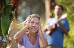 Надоеданная женщина покрывая ее уши Стоковая Фотография RF
