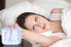 Надоеданная сонная молодая женщина поворачивает будильник, плохое пробуждение Стоковые Изображения