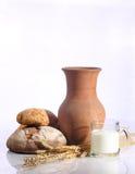 Надоите в прозрачной кружке и свежем хлебе на белой предпосылке Стоковые Фото
