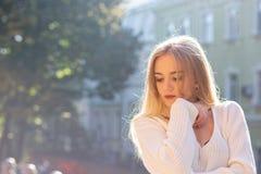 На открытом воздухе портрет внушительной модели нося стильное обмундирование представляя на улице с естественным светом солнца Пу стоковые фото