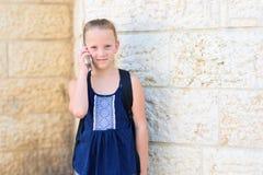 На открытом воздухе портрет говорить счастливой девушки 8-9 - летний по телефону стоковое фото