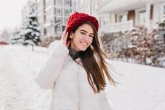 На открытом воздухе портрет довольной длинн-с волосами дамы в красной связанной шляпе идя вниз по улице в снежные выходные Фото  стоковые изображения