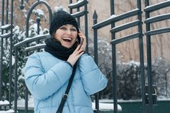 На открытом воздухе портрет зимы зрелой женщины с мобильным телефоном на снежной улице города, говорить женщины усмехаясь стоковые изображения rf