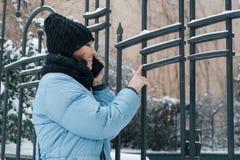 На открытом воздухе портрет зимы зрелой женщины с мобильным телефоном на снежной улице города, говорить женщины усмехаясь стоковая фотография rf