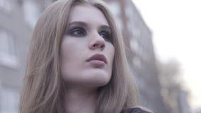 На открытом воздухе портрет красоты молодой коричневой с волосами девушки рассматривая в сторону запачканная линия города предпос акции видеоматериалы
