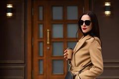 На открытом воздухе портрет молодой привлекательной стильной женщины нося соответствующие аксессуары, бежевое ультрамодное пальто стоковые изображения