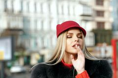 На открытом воздухе портрет нежной женщины нося стильную красную крышку и kni стоковое изображение