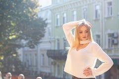 На открытом воздухе портрет роскошной модели нося стильное обмундирование представляя на улице с естественным светом солнца Пусто стоковое фото