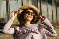 На открытом воздухе портрет счастливой загоренной модели носит шляпу и солнечные очки, наслаждаясь солнечной погодой стоковые изображения rf