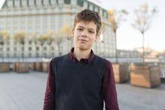 На открытом воздухе портрет усмехаясь мальчика 14 подростка, 15 лет Предпосылка города, золотой час стоковое фото rf