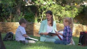 На открытом воздухе урок, счастливые учащийся мальчик одноклассника и девушка с книгами и болтовней воспитателя женскими прочитан акции видеоматериалы