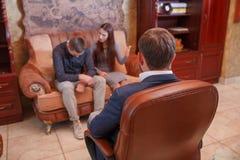 На парах психолога молодых сидя на софе, разрешите проблему, доктора делая примечания Стоковые Фотографии RF