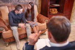 На парах психолога молодых сидя на софе, разрешите проблему, доктора делая примечания Стоковое Фото