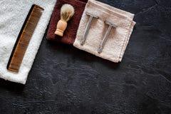 На парикмахерскае Бритвы, брея щетка, гребень и полотенце на черном copyspace взгляд сверху предпосылки Стоковое Фото