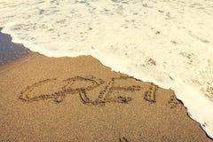 Надпись Крита на песке стоковые фото