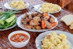 На плетеных плитах таблицы с частями shish kebab, каши и овощей стоковая фотография
