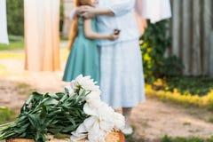 на пне букет белых пионов на заднем плане, бабушка, стойки пожилые женщины и обнимает ее внучку, стоковое изображение