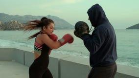 На побережье женщины в перчатках бокса выполняет дуновения с тренером акции видеоматериалы