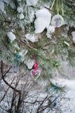 На покрытой снег ветви рождественских елок, украшения рождества висят в форме прозрачных шариков, сердец войлока Стоковая Фотография RF