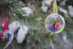 На покрытой снег ветви рождественских елок, украшения рождества висят в форме прозрачных шариков, сердец войлока Стоковое фото RF
