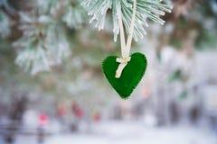 На покрытой снег ветви рождественских елок, украшения рождества висят в форме прозрачных шариков, сердец войлока Стоковая Фотография