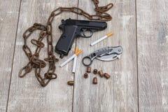 На поле план от цепи, пистолета, боеприпасов, ножа и нескольких сигарет Стоковые Фото
