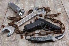 На поле цепь, пистолет, боеприпасы, старый ключ и факел Стоковое Изображение