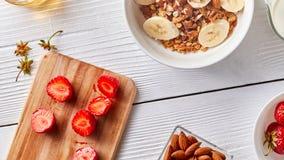 На половинах доски кухни зрелых клубник, плиты с granola и банана, гаек миндалин на белой кухне Стоковая Фотография RF