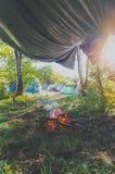 На поле лагерь и осветил огонь под тентом Стоковые Изображения RF