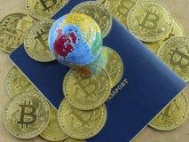 На предпосылке коричневых монеток Bitcoins картона, голубого паспорта, и глобуса Концепция финансовой независимости везде внутри стоковое изображение
