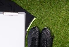 На предпосылке травы, лож футболка спорт, ботинок и таблетки для записи Стоковое Изображение RF