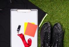 На предпосылке травы, лож футболка спорт, ботинок, таблетки записи, свистка и карточек штрафа для судьи, на fo Стоковые Фотографии RF