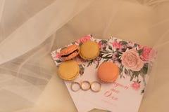 На приглашении свадьбы лежа 4 macaroons печенья и обручального кольца венчание Стоковые Изображения