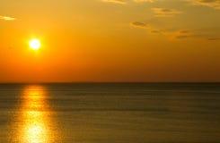 над ровным заходом солнца моря Стоковые Изображения
